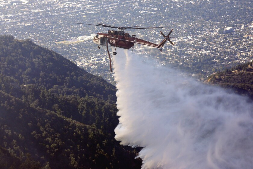 A helicopter makes a water drop on a fire near the Mt. Wilson Observatory.