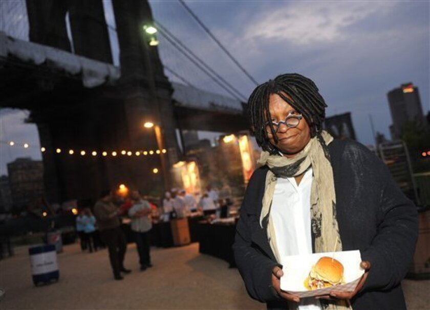 Whoopi Goldberg poses with a burger at the New York City Wine and Food Festival's Burger Bash, Friday, Sept. 30, 2011, in the Brooklyn borough of New York. (AP Photo/Diane Bondareff)