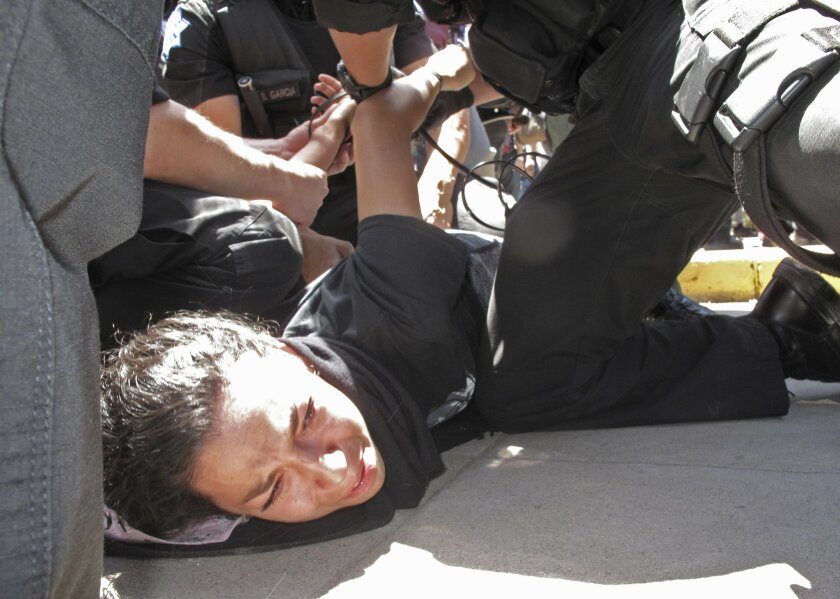 Police officers arrest a woman after a Republican presidential candidate Donald Trump rally in Fresno, Calif., on Friday, May 27, 2016. Police officers told hundreds of protesters to clear the streets in downtown Fresno following the Trump rally. Officers dressed in riot gear arrested two people on