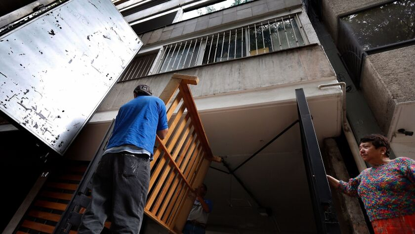 Movers haul away a bed frame from a condemned building in the popular Condesa neighborhood of Mexico City.