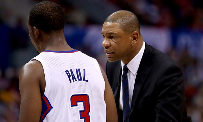 Clippers Coach Doc Rivers, right, speaks to point guard Chris Paul during a win over the Golden State Warriors on Oct. 31. Paul says he and Rivers share a desire to win.