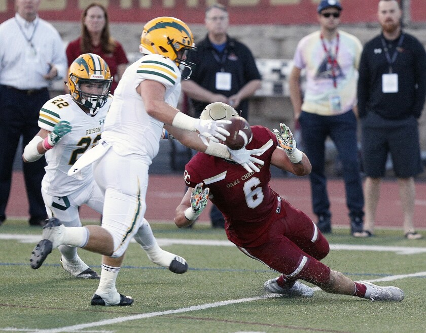 Edison High linebacker Cameron Eden gets his hands on the ball to knock it into the air and intercept it in a nonleague game at Westlake Village Oaks Christian High on Aug. 24, 2018.