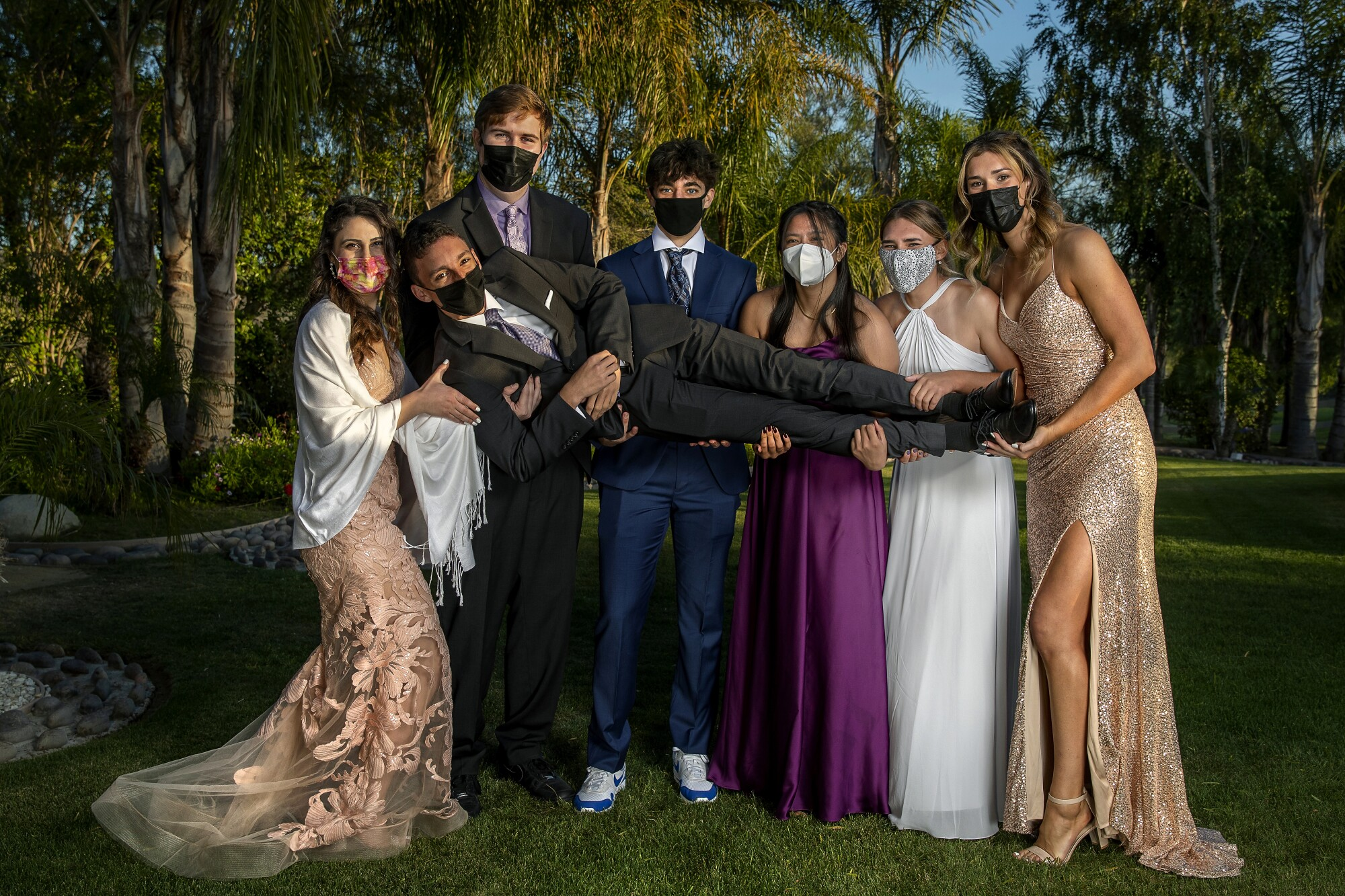 Students in formal wear and masks hoist a classmate off the ground.