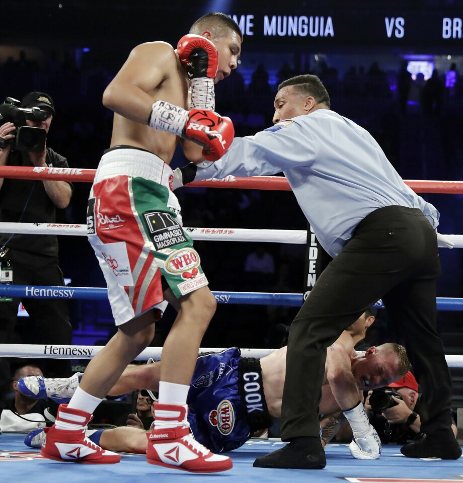 Referee Tony Weeks steps between Jaime Munguia, left, and Brandon Cook as Cook falls to the mat during their WBO junior middleweight championship boxing match, Saturday, Sept. 15, 2018, in Las Vegas. Munguia won by TKO.