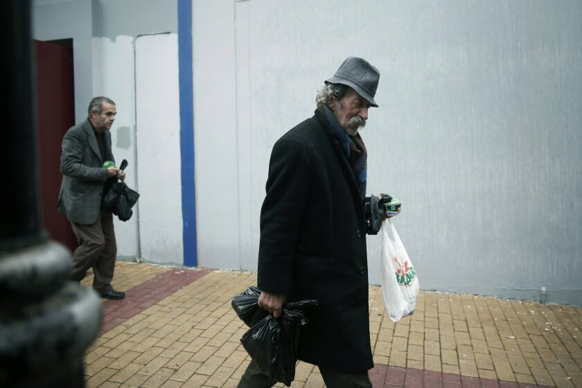 A man carry bags of donated food as he leaves with a meal for the homeless organized by the municipality of Athens on Wednesday Jan. 1, 2014. Homelessness has increased dramatically during the financial crisis in Greece, which has depended on international rescue loans for more than three years. (A