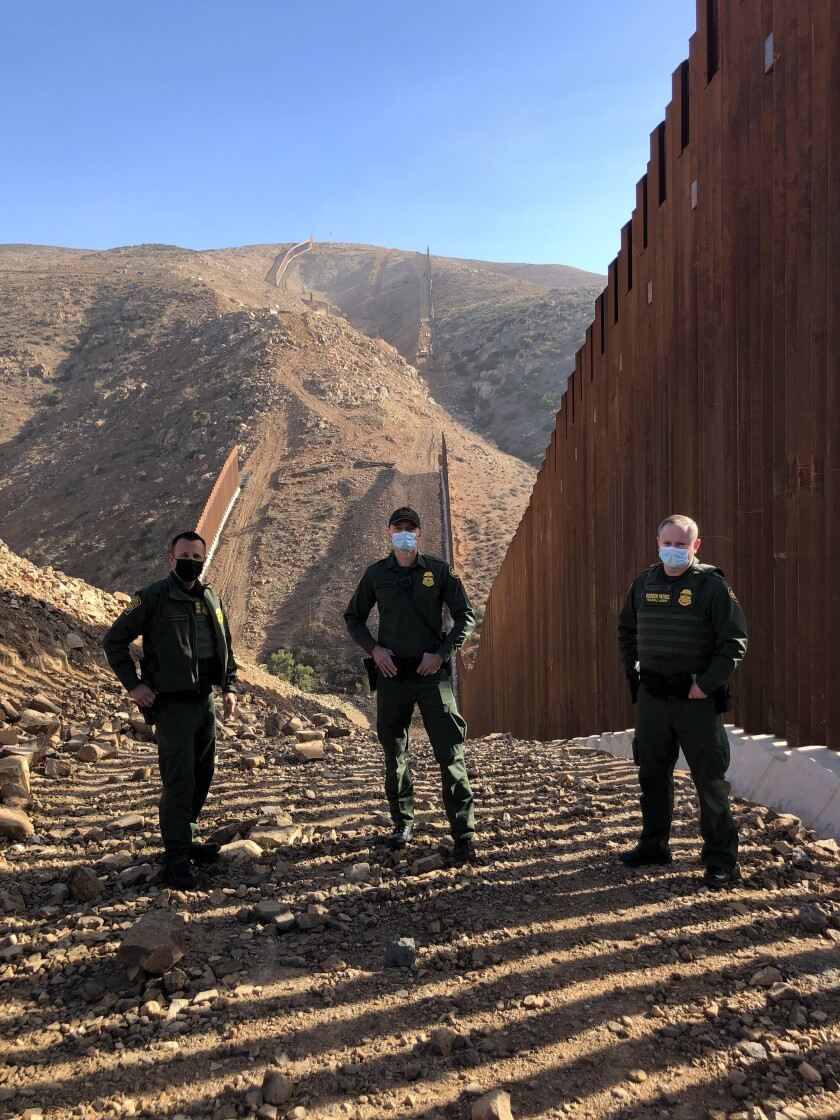 Border Patrol's Jeff Stephenson, Jacob MacIsaac and Gary Richards stand before a section of border wall in Otay Mesa, Calif.