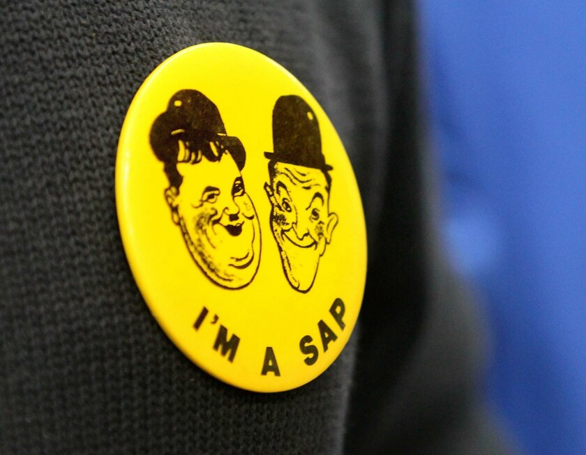 """Detail view of a club button of the """"Saps at Sea,"""" the San Diego """"tent"""" of the """"Sons of the Desert"""" social club, that shows Laurel and Hardy."""