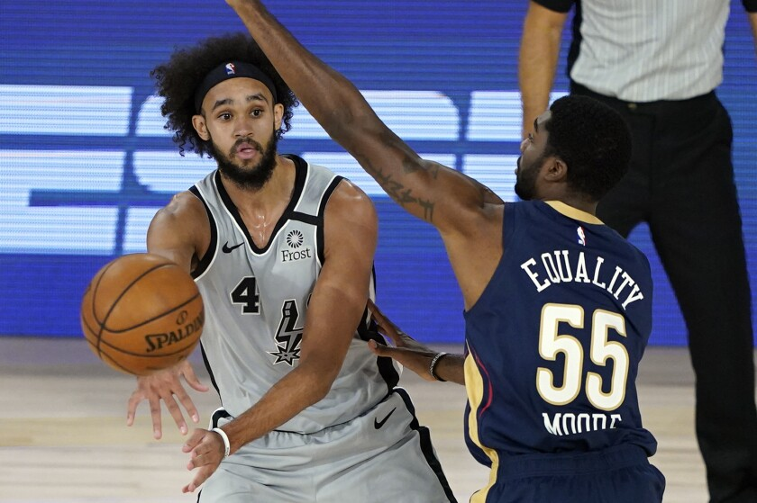 Derrick White (4) de los Spurs de San Antonio pasa el balón ante E'Twaun Moore (55) de los Pelicans de Nueva Orleáns, el domingo 9 de agosto de 2020, en Lake Buena Vista, Florida. (AP Foto/Ashley Landis, Pool)