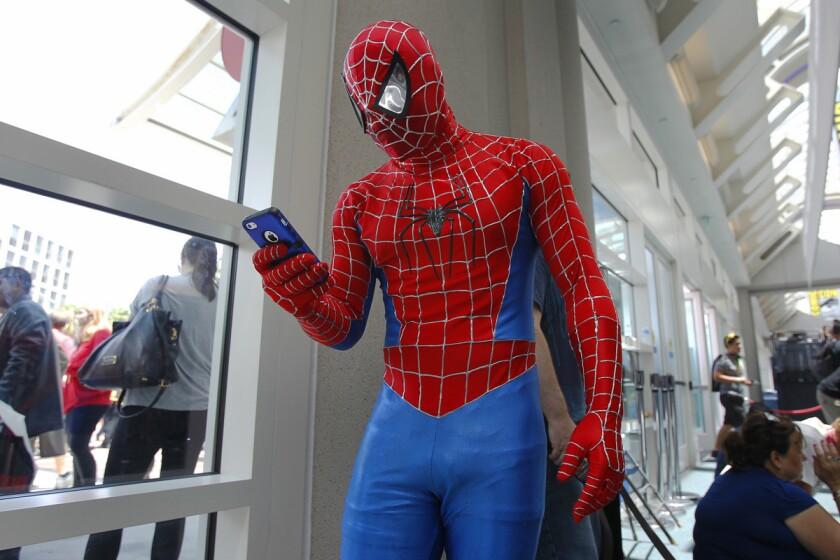 Tyson Brown as Spiderman checks his phone at Comic Con in 2014. (K.C. Alfred/Union-Tribune)