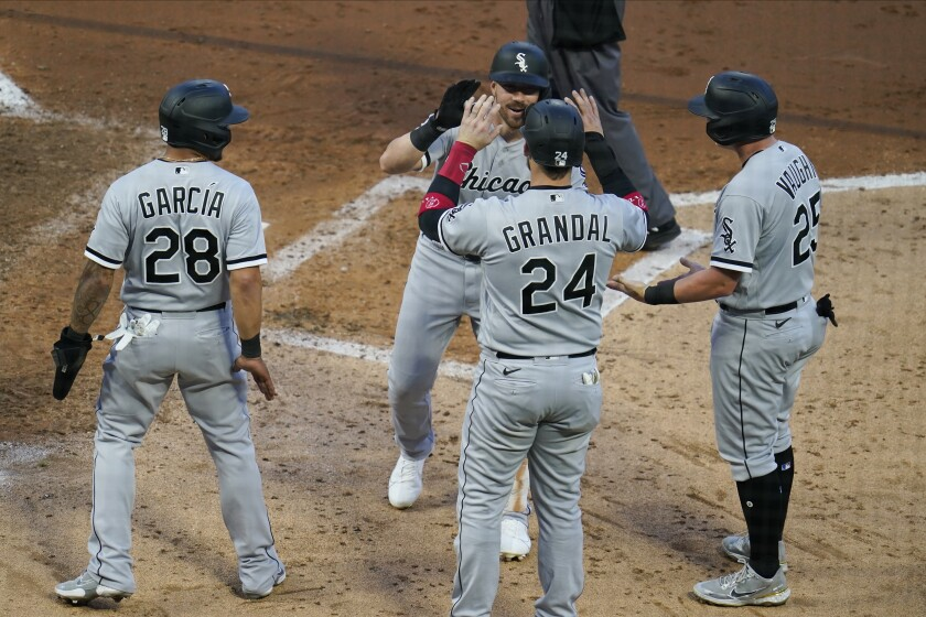Chicago White Sox's Danny Mendrick, center back, is greeted after his grand slam off Minnesota Twins pitcher Derek Law in the fifth inning of a baseball game, Monday, May 17, 2021, in Minneapolis. (AP Photo/Jim Mone)