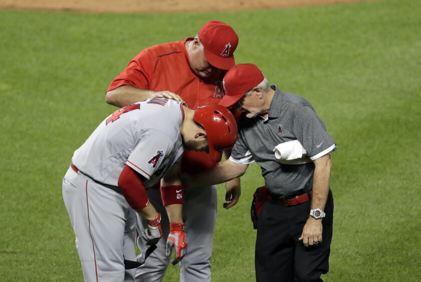 Los Angeles Angels' C.J. Cron, left, is tended to after being hit by a pitch in the sixth inning of a baseball game against the Baltimore Orioles in Baltimore, Friday, July 8, 2016. Cron left the game with a fractured bone in his left hand.(AP Photo/Patrick Semansky)