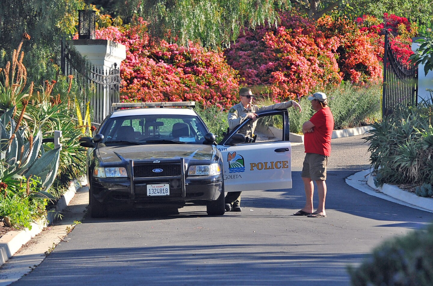 A Goleta police officer stands guard near the doctor's home on Greenhill Way.
