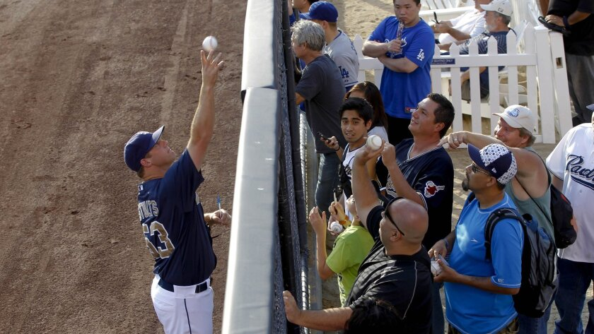 Padres pitcher Eric Stults tosses a ball to fans.
