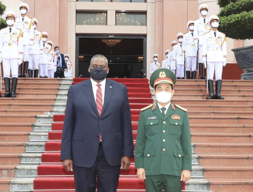 U.S Defense Secretary Lloyd Austin and Vietnamese Defense Minister Phan Van Giang stand for a photo in Hanoi, Vietnam, Thursday, July 29, 2021. Austin is seeking to bolster ties with Vietnam, one of the Southeast Asian nations embroiled in a territorial rift with China, during a two-day visit. (Nguyen Trong Duc/VNA via AP)