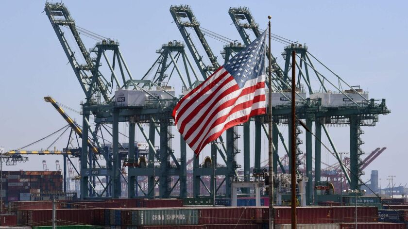 The U.S. flag flies over Chinese shipping containers unloaded at the Port of Long Beach.
