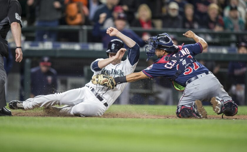 Seattle Mariners' Seth Smith, left, is tagged out at home plate by Minnesota Twins catcher Juan Centeno during the sixth inning of a baseball game  Saturday, May 28, 2016, in Seattle. (AP Photo/Stephen Brashear)