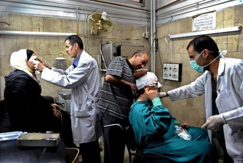 In this photo released by the Syrian official news agency SANA, Syrian doctors treat citizens who were injured in an  explosion, in the central district of Marjeh, Damascus, Syria, Tuesday April 30, 2013. A powerful explosion rocked Damascus on Tuesday, causing scores of casualties, a day after the