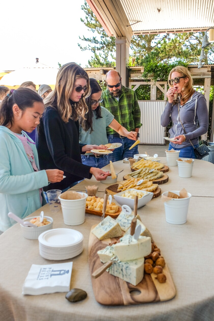 People gather around a table as they taste cheese