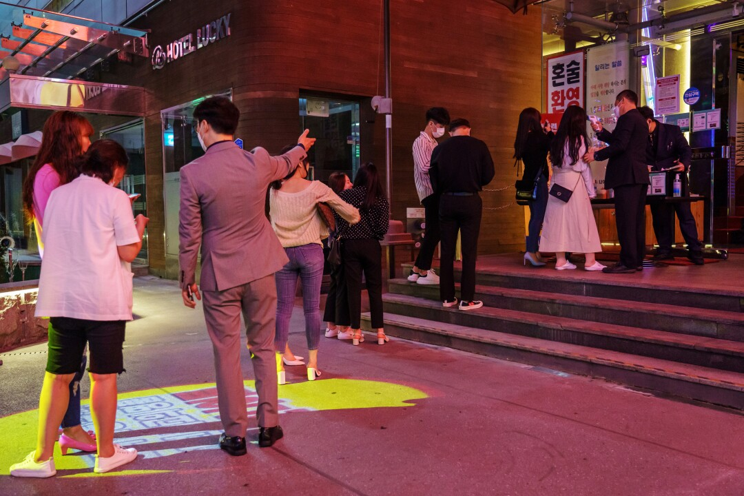 A line stretches outside Nightclub Seven in Daejeon, South Korea, as customers learn about the new QR code registry.