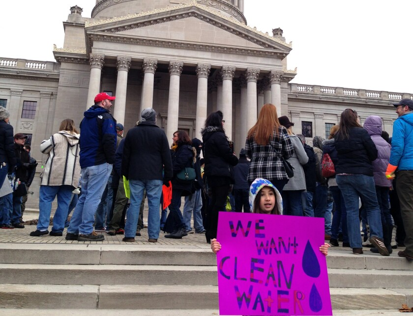 Emma Del Torto of Charleston, W.Va., holds a sign during a demonstration at the state Capitol on Jan. 18. More than 100 people gathered to question the safety of their tap water.