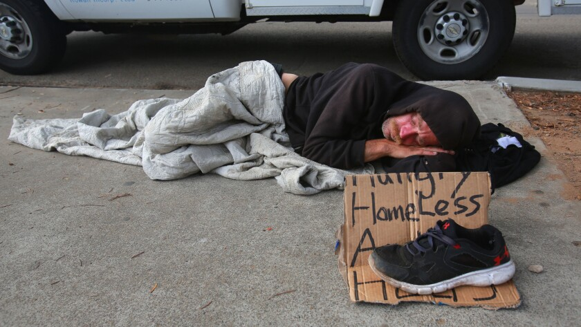 A man named Jerry sleeps on the sidewalk in downtown San Diego.