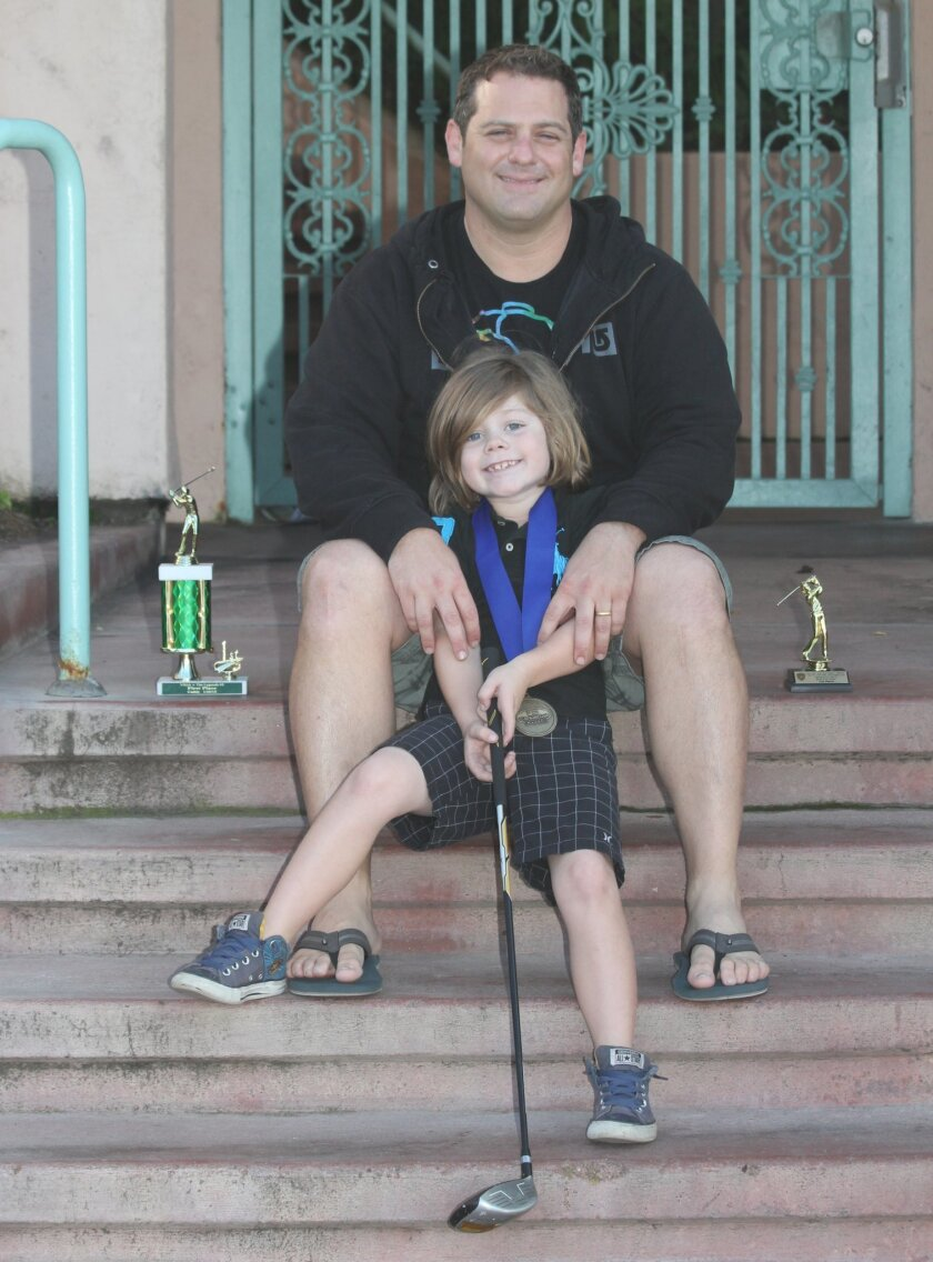 La Jolla Elementary School first-grader Daniel Chazen poses with some of his golf trophies and his father, Ben Chazen.