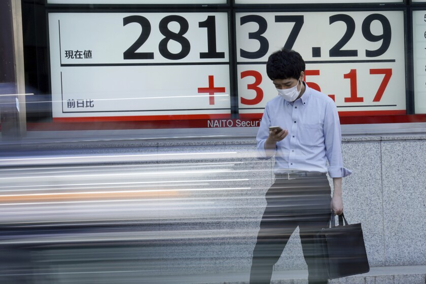 A man wearing a protective mask stands in front of an electronic stock board showing Japan's Nikkei 225 index at a securities firm Wednesday, Oct. 6, 2021, in Tokyo. Asian shares slipped in cautious trading Wednesday, shrugging off a rally on Wall Street, with Tokyo's Nikkei 225 index falling back after opening higher. (AP Photo/Eugene Hoshiko)