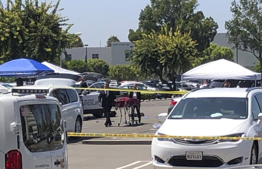 Orange County coroners remove a body of a stabbing victim from a parking lot from a parking lot at California State University, Fullerton on Monday, Aug. 19, 2019. An employee of the university was killed in a stabbing in a campus parking lot Monday in what police called a targeted attack, though they were not sure of a motive. The victim was in his late 50s and worked in international student admissions at the sprawling campus in Orange County, police Lt. Jon Radus said. He was not immediately identified by authorities.