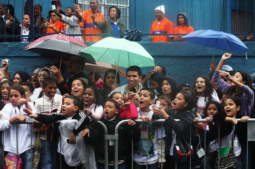 Children cheer Thursday as Pope Francis tours the Varghina favela, or shantytown, in Rio de Janeiro. In the aftermath of the pope's visit, some residents said little changed in their lives.