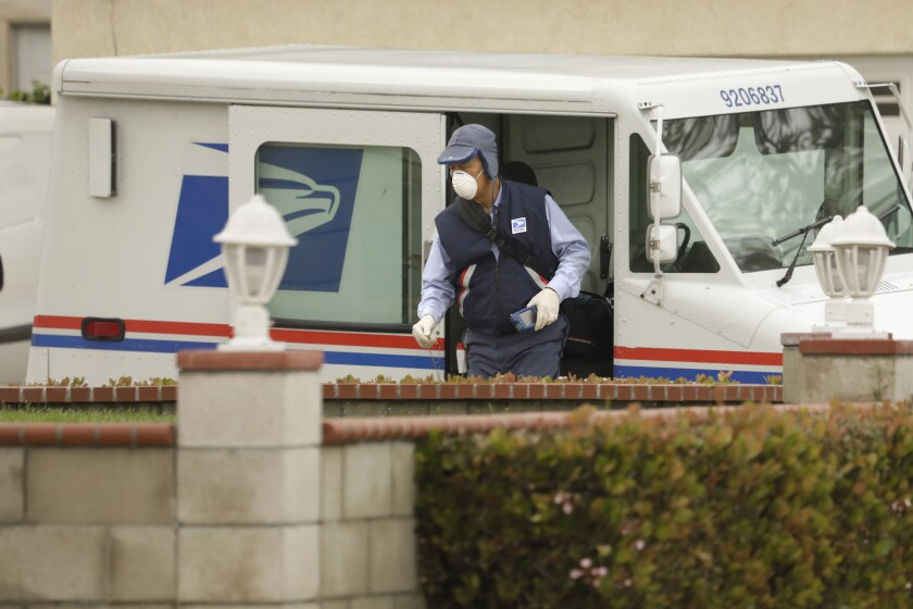 A postal worker wearing a mask and gloves delivers mail in Torrance on March 14.