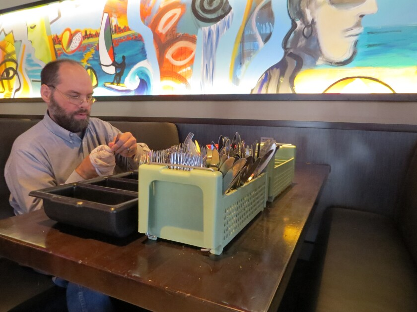Douglas Need, 46, of Escondido polishes silverware at The Yard House restaurant in Carlsbad on Dec. 19. Yard House recent won a state award for its longtime practice of hiring workers with disabilities like Need.