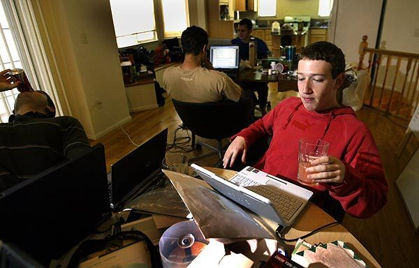 Mark Zuckerberg, right, and friends work on Thefacebook.com, an early version of Facebook, in a rented home in Los Altos, Calif., in January 2005. Zuckerberg launched the social network in his Harvard dorm room in the previous year. It soon spread to more than 300 colleges and universities and grew to more than a million members.
