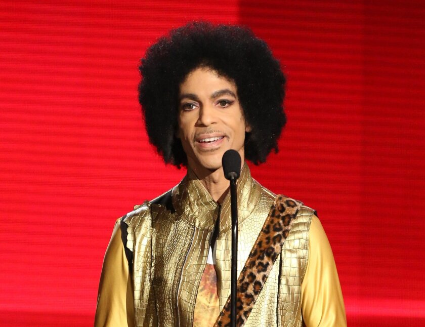 FILE - In this Nov. 22, 2015 file photo, Prince presents the award for favorite album - soul/R&B at the American Music Awards in Los Angeles. A law-enforcement official says that tests show the music superstar died of an opioid overdose. Prince was found dead at his home on April 21, 2016, in subur