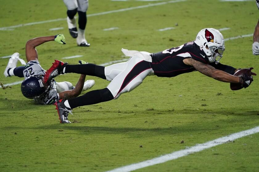 El wide receiver de los Cardinals de Arizona Christian Kirk se lanza para un touchdown ante la defensiva del cornerback de los Seahawks de Seattle Quinton Dunbar, en la segunda mitad del juego del domingo 25 de octubre de 2020, en Glendale, Arizona. (AP Foto/Ross D. Franklin)