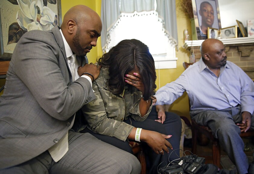 Attorney Damario Solomon-Simmons comforts Tiffany Crutcher, twin sister of Terence Crutcher, who was shot and killed by police in Tulsa, Okla., on Friday. At right is the Rev. Joey Crutcher, the twins' father.