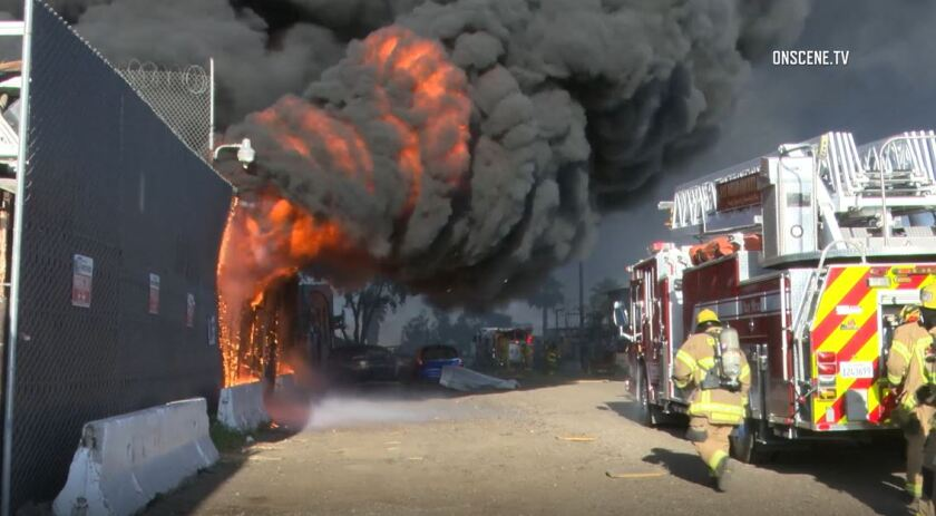 Firefighters battle a huge blaze that broke out at an auto junkyard Friday evening in Otay Mesa.