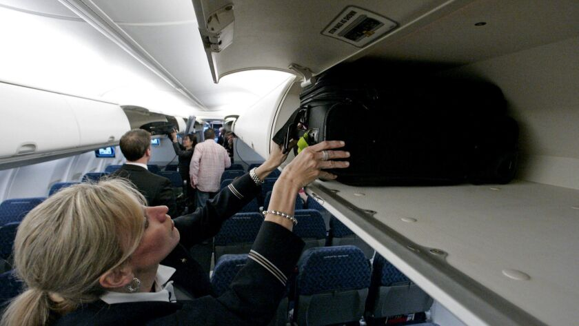 American Airlines flight attendant Renee Schexnaildre stows a bag in an overhead bin on a Boeing 737-800 jet at Dallas Fort Worth International Airport. The carrier will allow basic economy fliers one free carry-on bag starting Sept. 5.