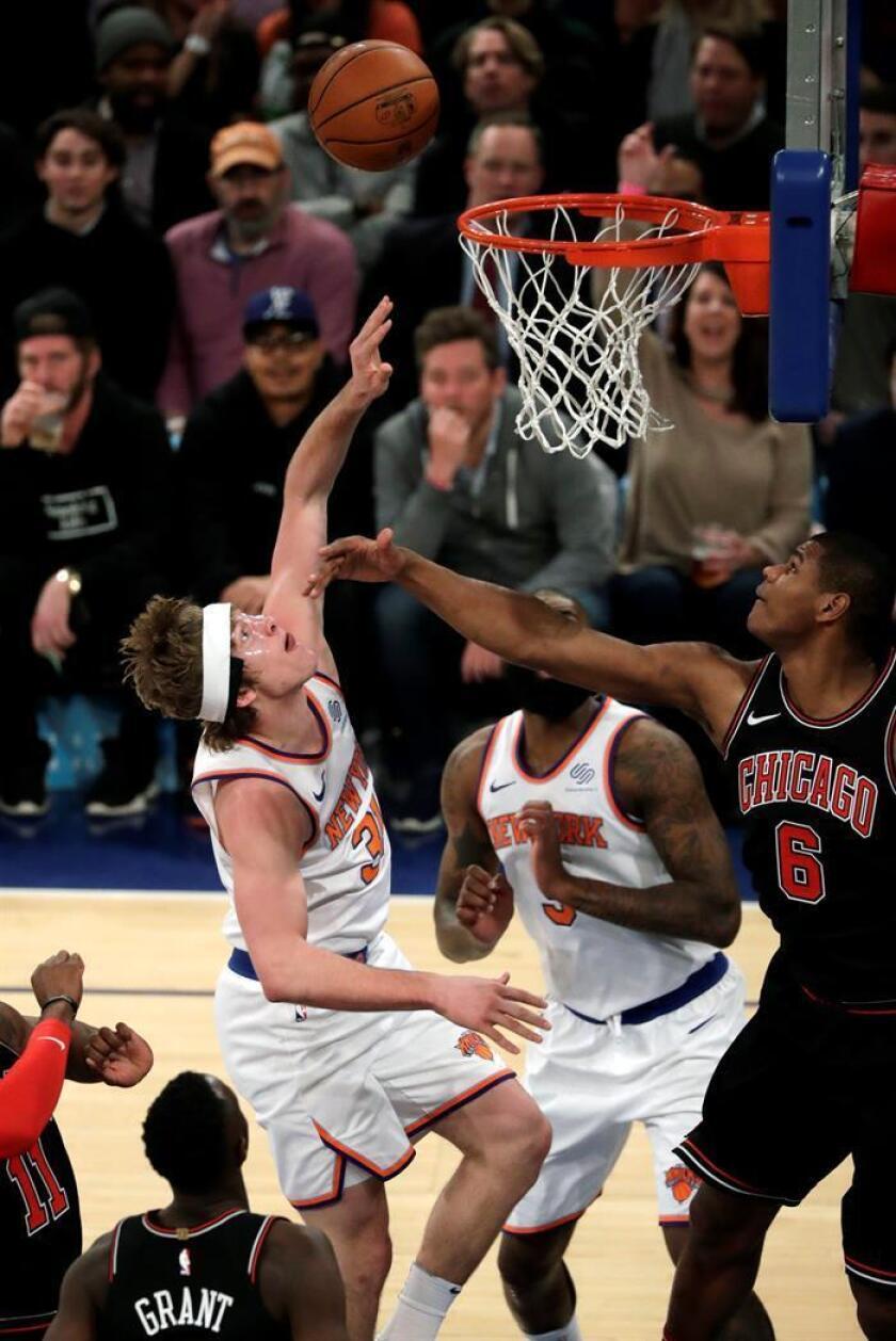 El jugador Ron Baker (i) de New York Knicks intenta lanzar ante Cristiano Felicio (d) de Chicago Bulls, durante un partido entre Chicago Bulls y New York Knicks de la NBA, que se disputa en el Madison Square Garden, en Nueva York (Estados Unidos). EFE