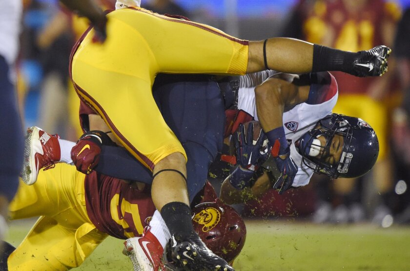 Arizona wide receiver Nate Phillips, right, is tackled by Southern California linebacker Osa Masina, bottom, and another player during the first half of an NCAA college football game, Saturday, Nov. 7, 2015, in Los Angeles. (AP Photo/Mark J. Terrill)