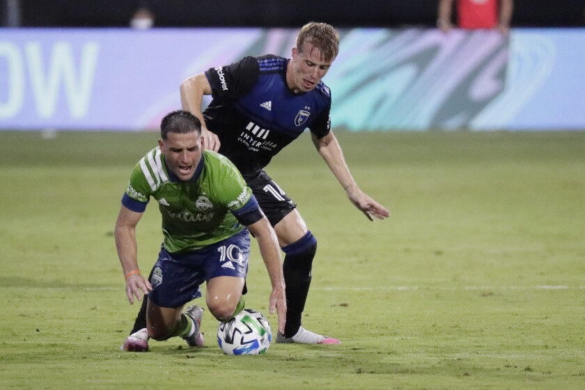 Seattle Sounders midfielder Nicolas Lodeiro (10) goes down as he battle for the ball against San Jose Earthquakes midfielder Jackson Yueill during the second half of an MLS soccer match, Friday, July 10, 2020, in Kissimmee, Fla. (AP Photo/John Raoux)