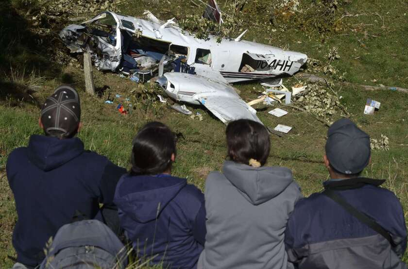 People look at the wreckage of a Piper PA-60 Aerostar twin-engine aircraft that crashed near San Pedro de los Milagros, east of Medellin, Colombia. The plane's three occupants were making a movie starring Tom Cruise. Two died.