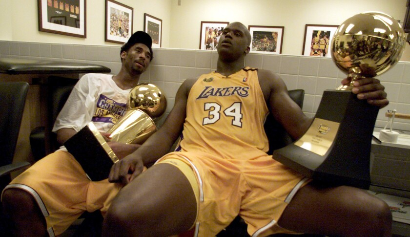 Kobe Bryant and Shaquille O'Neal, holding the NBA and MVP trophies, won their first title together in 2000.