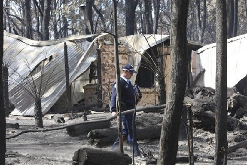 Police inspect a farm house destroyed by wildfires in Whittlesea, Australia, Monday, Feb. 9, 2009. The deadliest wildfires in Australia's history burned people in their homes and cars and wiped out entire towns, officials discovered Monday as they reached farther into the fire zone. Suspicions that the worst wildfires ever to strike Australia were deliberately set led police to declare crime scenes Monday in towns incinerated by blazes, while investigators moving into the charred landscape discovered more bodies. The death toll stood at 130.(AP Photo/Trevor Pinder, POOL)