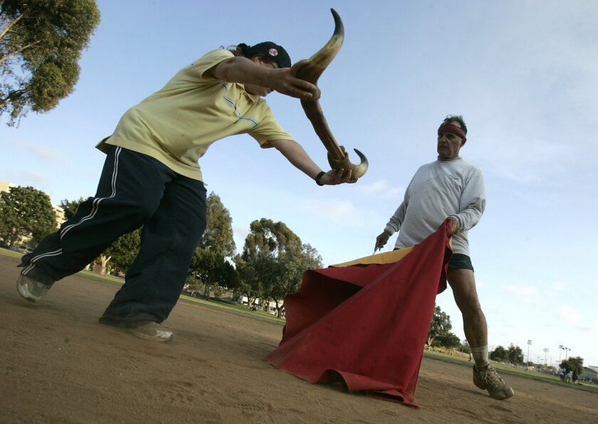 Peter Rombold of Lemon Grove practices bullfighting as wife Tricia plays along before today's event in Tijuana.  (Earnie Grafton / Union-Tribune)