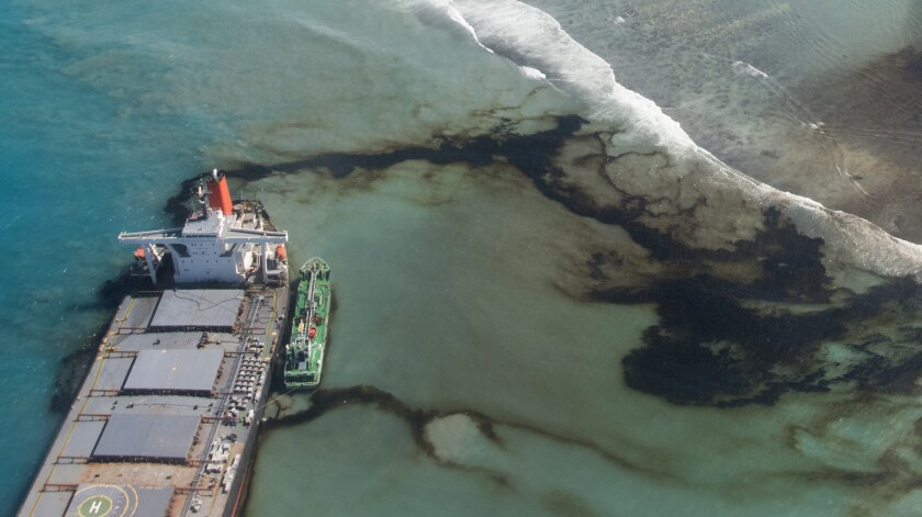 This photo provided by the French Army shows oil leaking from the MV Wakashio, a bulk carrier ship that ran aground off the southeast coast of Mauritius, Tuesday Aug.11, 2020. Thousands of students, environmental activists and residents of Mauritius were working around the clock trying to reduce the damage to the Indian Ocean island from an oil spill after a tanker ran aground on a coral reef. An estimated 1 ton of oil from the Japanese ship's cargo of 4 tons has already escaped into the sea, officials said. (Gwendoline Defente, EMAE via AP)