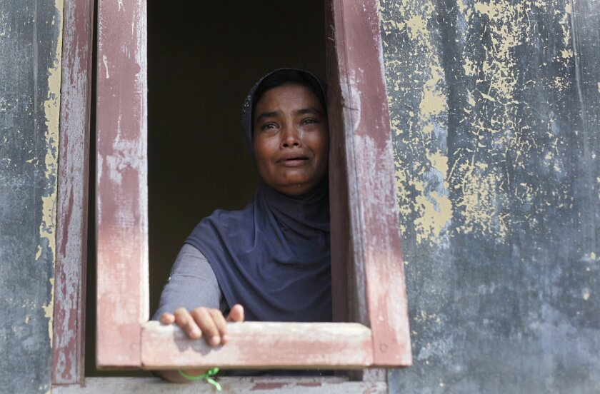An ethnic Rohingya woman weeps as she looks outside from a window at a temporary shelter for the migrants whose boats washed ashore on Sumatra island on Sunday, in Lapang, Aceh province, Indonesia, Wednesday, May 13, 2015. More than 1,600 migrants and refugees have landed on the shores of Malaysia