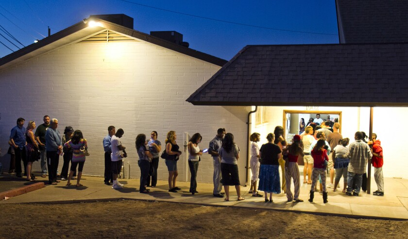 People wait in line to vote at polling place located in a church in Phoenix.