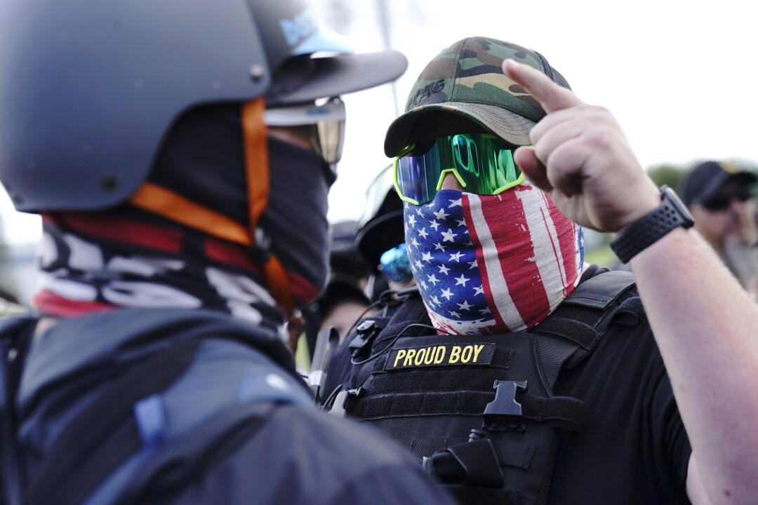 A man in a U.S. flag mask and tactical vest with a Proud Boy patch points into the masked face of a counter-protester