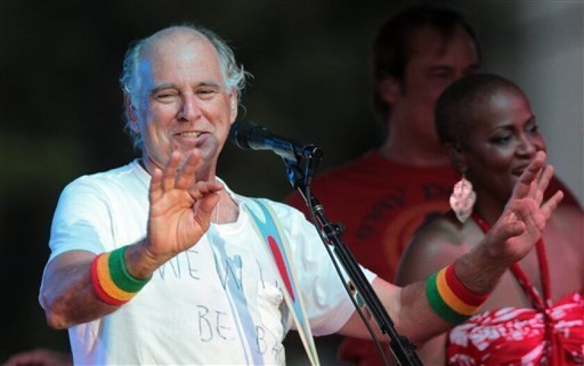 Jimmy Buffett talks about the oil spill to his audience in Gulf Shores, Ala., Wednesday, June 30, 2010. Buffet postponed his free concert on the beach Thursday night because of the possibility of bad weather spawned by Hurricane Alex and played instead on Wednesday at his sister's restaurant. (AP Photo/Dave Martin)