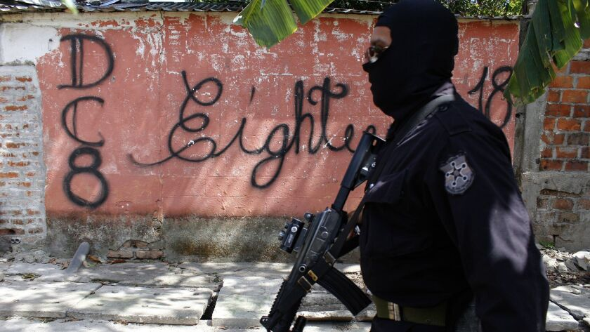 In this April 5, 2016 photo, a masked and armed policeman patrols a gang controlled neighborhood in